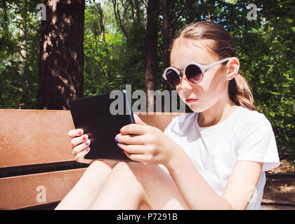 Cute smiling girl in white t-shirt avec un gadget mobile en mains assis sur un banc. Banque D'Images