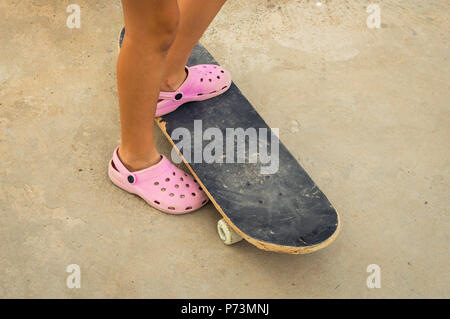 Petite fille portant des sabots en plastique rose sur une planche à roulettes. Apprendre à patiner. Banque D'Images