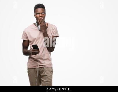 Young african american man wearing headphones holding smartphone et couvrir la bouche à part choqué avec honte pour erreur, expression de la peur, peur