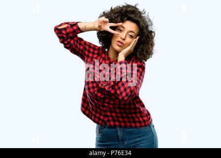 Belle femme arabe à la caméra à l'intermédiaire de doigts en un clin d'œil le geste de la victoire et en soufflant un baiser Banque D'Images