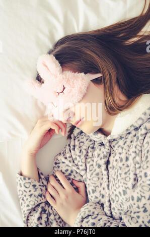 Belle jeune femme en masque de sommeil mignon pyjama chaud et couché dans le lit et dormir le matin. Vue d'en haut. Banque D'Images