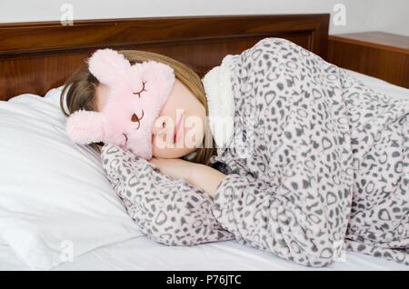 Belle jeune femme en masque de sommeil mignon pyjama chaud et couché dans le lit et dormir le matin. Banque D'Images