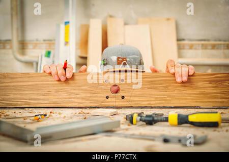 Menuisier expérimenté dans les vêtements de travail et de petites marques buiness propriétaire est un bloc de bois pour fabriquer des meubles dans un atelier de lumière vue latérale, à l'arrière Banque D'Images