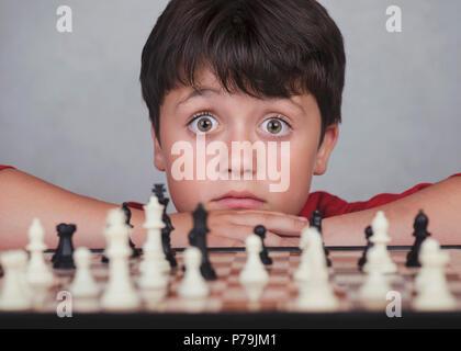 Petit Garçon jouant aux échecs sur fond gris Banque D'Images