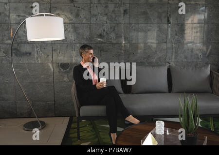 Man sur le canapé et parler au téléphone Banque D'Images