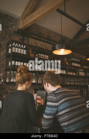 Couple le téléphone mobile dans le restaurant Banque D'Images