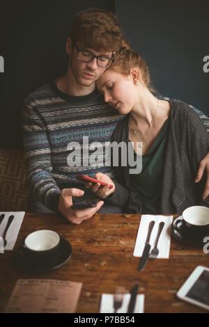 Couple et l'utilisation de téléphones mobiles dans le café Banque D'Images