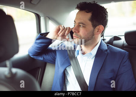 Businessman talking on mobile phone in a car Banque D'Images