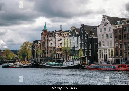 Amsterdam, Pays-Bas - 27 avril, 2017: péniches et barges vivant dans Binnenamstel contre canal néerlandais typiques maisons avec pavillon de l'Allemagne et