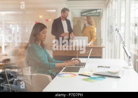 Femme graphic designer using laptop at desk