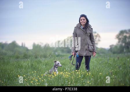 Femme mature avec son chien dans le champ, portrait Banque D'Images