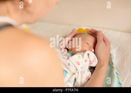 Mère réconforter un bébé nouveau-né après avoir changé une couche Banque D'Images