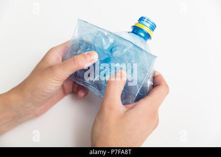 Bouteille en plastique bleu écrasé dans woman's hands sur fond blanc. Concept de la pollution Banque D'Images