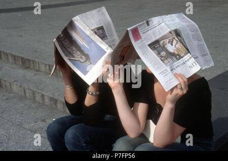 Les jeunes avec des journaux au-dessus de leurs têtes, Berlin, Allemagne Banque D'Images