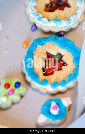 Le bac papier de cadeau fort remplis de beaucoup de givrage décoré avec des bonbons colorés sucre émaillés bleu artificiel de vacances de Noël fait maison de boulangerie sprinkles cooki Banque D'Images