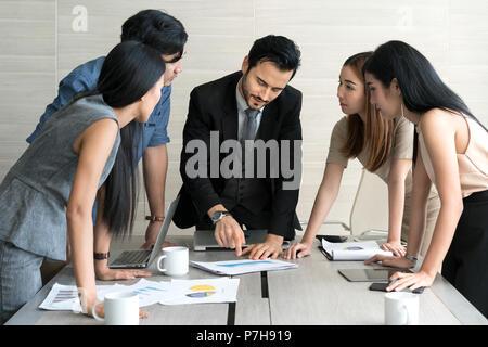 Smart manager expliquant réunion interne à son équipe de projet dans un bureau moderne. Le groupe ethnique de personne d'affaires en litige. Projet et Business c Banque D'Images