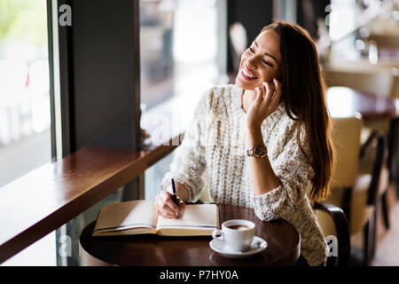 Portrait of happy young woman in cafe Banque D'Images