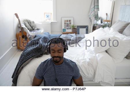 Jeune homme méditant sereine avec des écouteurs dans la chambre Banque D'Images