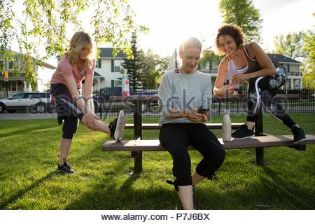 Senior female runner stretching et amis à l'aide de smart phone in park Banque D'Images