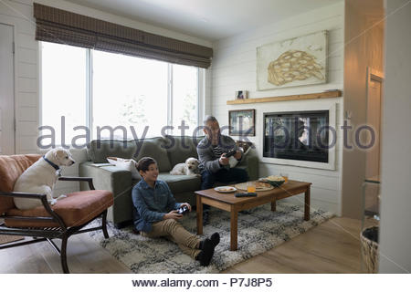 Regarder les chiens father and son playing video game in living room Banque D'Images