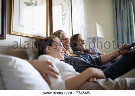 Tendre mère et filles adolescentes en regardant la télé on bed Banque D'Images