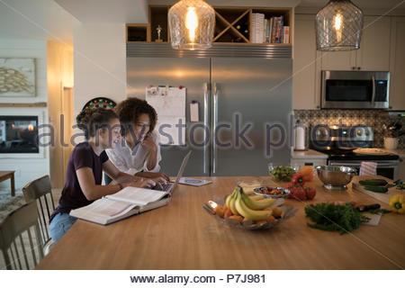 Fille mère aidant à faire leurs devoirs à l'interpolation de l'ordinateur portable dans la cuisine Banque D'Images
