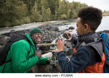 Fils de téléphone appareil photo photographier père ludique sur une plage Banque D'Images