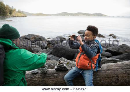 Fils de téléphone appareil photo photographier père sur plage robuste Banque D'Images