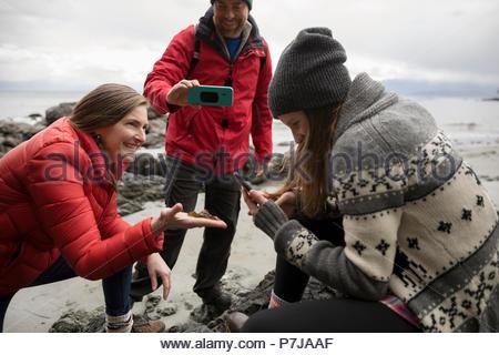 Famille avec les téléphones avec appareil photo sur une plage Banque D'Images