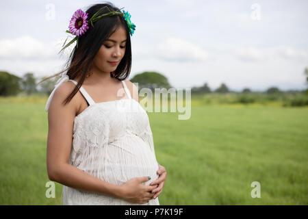 Heureux et fier pregnant Asian woman looking at son ventre dans un parc au lever du soleil
