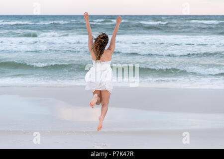 Jeune femme heureuse en robe blanche sur la plage soleil rose en Floride avec le vent, les vagues de l'océan, le saut à la mi-course l'air à l'eau Banque D'Images