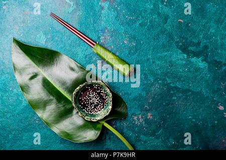 Concept d'aliments asiatiques. Chopstick et soysauce sauce soja sésame blanc avec sur fond bleu turquoise avec des feuilles tropicales . Vue d'en haut. Banque D'Images