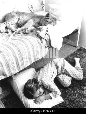 Jeune Lion dort dans un berceau, la jeune fille sur le sol, en Angleterre, Grande-Bretagne Banque D'Images