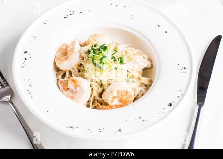Les pâtes Spaghetti Carbonara avec du fromage, des langoustines et des verts en plaque blanche Banque D'Images