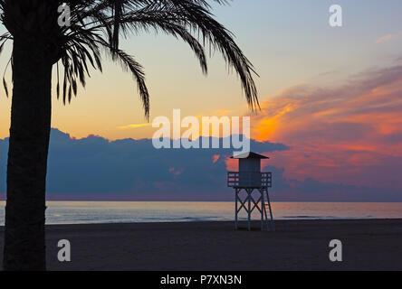 Nuageux lever du soleil sur la plage de la mer Méditerranée dans la région de Valence de l'Espagne. Plage de sable fin avec palmiers et lifeguard chalet dans l'aube de l'anticipation. Banque D'Images