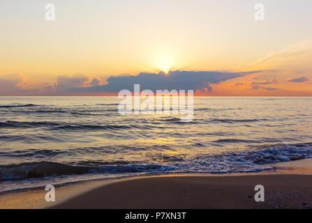 Bien au-dessus de nuages pendant l'aube sur la mer Méditerranée. Nuageux lever du soleil sur une plage de sable vide. Banque D'Images