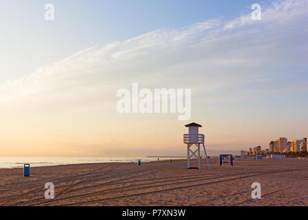 La plage de sable de mer au lever du soleil dans la région de Gandia, Valence, Espagne. Nuageux lever du soleil dans des tons orange sur la mer calme. Banque D'Images