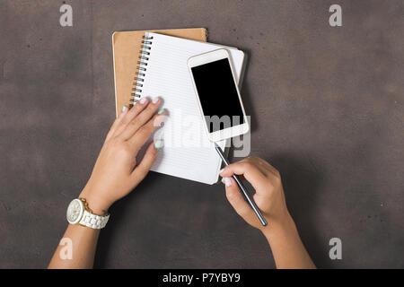 Les femmes d'écrire sur un ordinateur portable sur le lieu de travail. Mise à plat, vue du dessus. Lieu de travail féminin Concept Banque D'Images