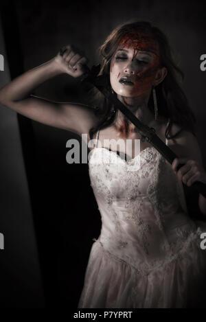 Lady Zombie corpse tenant un sabre pour tuer elle-même, alors qu'elle mariage. L'horreur et le concept de Ghost pour la journée de l'événement thème de l'Halloween. Et ton film Dark grunge Banque D'Images