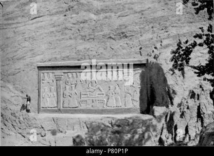 """Anglais: Rock Sculpture près de Shah-Abdul-Azim. Photographié par Arnold Henry Savage Landor, 1901, probablement en octobre. À partir de la page 244 de l'ensemble des terres convoitées. Landor's description: """"à droite de la route, à quelque distance avant d'atteindre la mosquée, un très original, grand haut-relief a été sculpté sur la face d'un énorme rocher et se reflète à l'envers dans un étang d'eau à son pied. Les hommes se baignaient ici dans des tiroirs rouge ou bleu, et des centaines d'ânes étaient des femmes voilées de convoyage vers cet endroit. Un arbre énorme fait de l'ombre sur la piscine de l'eau dans la matinée. Il est intéressant Banque D'Images"""