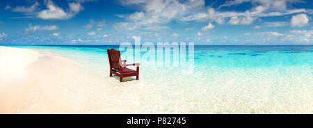Chaise en bois debout dans la mer sur la plage invitation au repos sur une île déserte, seule une large vue panoramique sur l'océan Banque D'Images