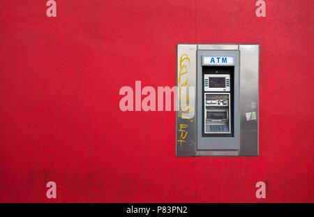 Un guichet automatique bancaire (GAB) est un contraste frappant sur le mur rouge vif où il est monté. Toronto, Ontario, Canada Banque D'Images