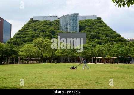 Un homme tond la pelouse centrale Tenjin en parc en face de l'éco-friendly ACROS building à Fukuoka, au Japon. Banque D'Images