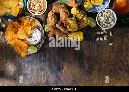 Le poulet frit, les sauces, les croustilles, nachos, arachides, pistaches et les craquelins sur une table en bois avec bordure, vue du dessus Banque D'Images