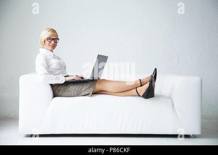 Certain blond businesswoman porte des lunettes assis sur le canapé en cuir élégant blanc avec ordinateur portable de travail Banque D'Images