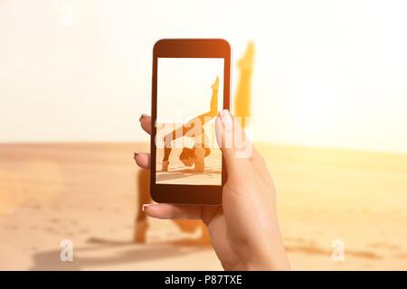 Femme de prendre une photo avec votre téléphone mobile une femme faisant un stunt acrobatique sur le sable Banque D'Images