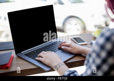 Femme de la saisie sur ordinateur portable avec écran vide avec l'exemplaire de l'espace pour votre texte ou le contenu publicitaire, assis à table en bois Banque D'Images