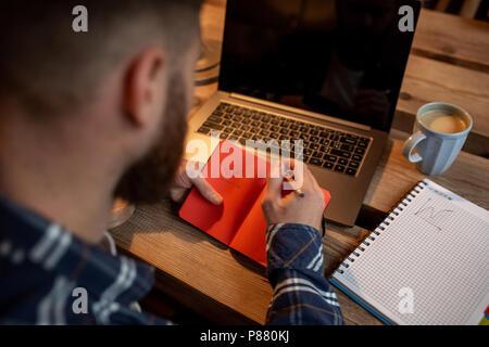 Portrait de jeune homme clavardage par net-book pendant le travail en pause café, homme assis devant l'ordinateur portable ouvert avec copie vierge de l'écran de l'espace. Banque D'Images