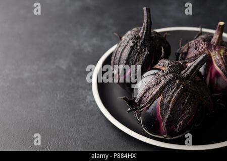Type Italien frais aubergines ou les aubergines avec de l'eau tombe dans la plaque noire sur fond noir en sombre Banque D'Images
