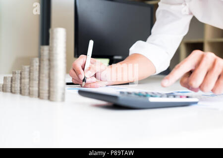 Des piles de pièces de comptabilité de l'entreprise avec le concept d'économiser de l'argent comptant, de prendre des notes de la calculatrice à la main, est écrit dans un cahier. Pièces empilées Banque D'Images